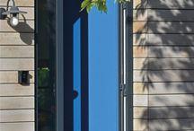 """ScanaBouw   Het huis met de blauwe deuren / Meestal heeft de warme uitstraling van een houtskeletbouw-woning zijn weerslag op het karakter van de bewoners, of is het nu andersom? De trotse, vroegste bewoners van een fraai duingebied onder de rook van Noordwijkerhout zijn Ocky en Max. Hun verhaal: """"Wij komen uit Leiden en we woonden eerder op diverse, bijzondere plekken, zoals in grachtenpanden, plantages, aan singels maar nu wilden we graag nog één keer wat ruimte creëren en volop tuingericht wonen."""