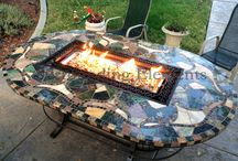 Mosaic Patio Dining Fire Pit Tables / Custom handcrafted mosaic patio tables designed for your backyard. Standard or custom designs, shapes and sizes available. Each hand-laid stone and porcelain mosaic table can be designed to function as: a Fire Pit, a Barbecue, an Ice Bucket, a Lazy Susan or a Solid Table. These centerpieces are interchangeable and can also be removed from the table and inserted into a side stand. Available table inserts includes: Glass Burner, Lazy Susan & Center Plug, Ice Bucket, and Fire Logs.