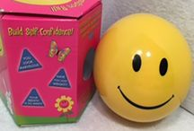 """Fun Version of the Magic 8 Ball / Sometimes life is kind of rough. Why wait for some kind soul to give you the praise you deserve? Just have the yellow 3 ¾"""" plastic Affirmation Ball handy next tie you're feeling blue. The happy face on the back will be smiling at you as you turn the ball for the next encouraging remark, such as, """"Your breath is so minty,"""" or, """"You look marvelous."""" Illustrated window box."""