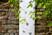 Cyanistes - The Curator Collection / Cyanistes is the Latin for bluetits, and this light and elegant #design, hand coloured using vivid tones, features this delicate little #bird fluttering around a fine network of lightly drawn branches.  A fresh yet distinctive design, Cyanistes looks enchanting either draped, hung or upholstered. Available on Oyster 100% Linen.  Four Colours – Original, Ink, Dust & Blush. Available on Flax Linen.  Two Colours – Original & Ink. #Wallpaper Available. #interiors #fabricinspiration #interiordesign
