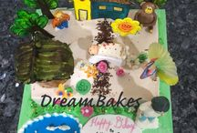 Village themed Cake / Village themed Cake with huts, trees, flowers, monkey, butterfly etc. The client also wanted to include a small baby.
