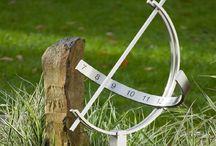 Sonnenuhr / Die Edelstahl-Sonnenuhr ist ein Zeitmesser, der seine Faszination aus dem astronomischen Kenntnisreichtum der Antike bezieht.  Das formschöne Modell aus zwei sich kreuzenden Halbkreisen ist eine Zierde für jeden Garten. Auf dem einen Halbkreis ist die Zahlenreihe angeordnet, während der andere den Stab hält, der den Schatten wirft.