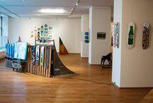 Talajfogás kiállítás és DIY gördeszka készítés / A Talajfogás tárlat kiállítóinak nagy része képzőművészeti oktatásban részesült és mindenkiről elmondható, hogy a gördeszkázást életvitel-szerűen űzi. A kiállításon láthatók voltak hazai gördeszkás videók, fotók, objektek, magazinok, illusztrációk és hozzájuk kapcsolódó irodalmi és zenei alkotások is. A Talajfogás kiállítás célja, hogy bemutassa, mára a gördeszkázás a mindennapi városi környezet vizuális tárgyaként és alternatív közlekedési eszközeként a fiatalok életvitelének részévé vált.