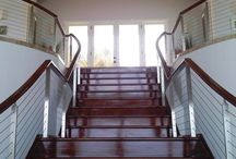 Long Bay, Antigua / Working with Horizons Construction Ltd. The Ithaca Style railing was chosen to mount to this interior curved staircase. We customized the stainless steel posts with a chamfered top and standoffs to support the wooden top rail.