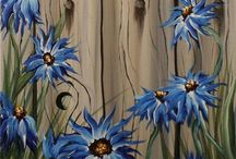 Blå blommor mot staket.