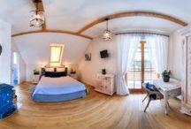 Pokój SZCZĘŚCIE / Pokój dwuosobowy z fantastycznym małżeńskim, pikowanym łożem. Utrzymany w tonacji niebiesko-białej, z akcentami namalowanych ziół na szafie i szafkach. Belkowany sufit, niebieska, stylowa koza, podbielane drewniane meble – nadają mu iście niebiański, szczęśliwy klimat. Pokój z balkonem i wspaniałym widokiem na ogród oraz panoramę wzgórz.  Pokój z klimatyzacją.