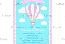 Special Delivery Hot Air Balloon Baby Shower Lilac / This collection features a purple hot air balloon with bunting. The background consists of clouds on sky blue, a scallop edged frame and purple stripes.