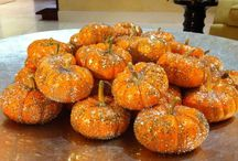 pumpkins center stage / This is just a fun easy way to make a lovely pumpkin splash on your dining room table from October through Halloween! Originally I saw one of these in a store window in Sedona, AZ and decided to give it a try. The trick is to use three different colors of glitter to add more interest. They look striking in a shallow bowl and especially outstanding twinkling in the sun. I used a silver lined bowl but gold, wood or glass would be equally nice.