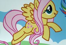 my little pony mural / This mural was painted in a bedroom nursery for a 7 month old baby girl. My little pony was chosen as a theme by her parents for a soft and gentle appeal. The room was initially pink and had to be painted back to white before I could begin drawing out the mural. The main characters would be on one wall, with a wrap round sky and hills on another wall.