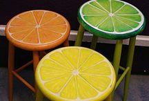 Bancos de madera redondos pintados como cítricos (limón amarillo, limón verde y naranja)