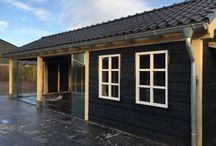 Tuinhuis Referentie / Eiken overkapping geplaatst in Nistelrode. Overkapping op maat gemaakt naar wensen van de klant. Het houten frame en de spanten zijn gemaakt van eikenhout. De wanden zijn bekleed met zwarte potdeksel-planken en 2 ramen aan de voorzijde. Het dak is afgewerkt zonder dakbeschot zodat de pannen vanuit de binnenzijde te zien zijn. Aan de rechterzijde is een extra afdak gemaakt voor het openhaardhout.