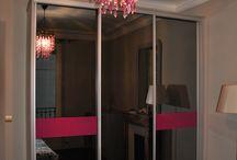 Rose et gris / placard coulissant habillé de portes coulissantes miroir gris, avec deux bandes de verre laqué fushia bord à bord. Feutré et chaleureux.