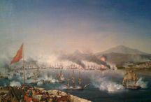 Ελληνική Επανάσταση / Η Ναυμαχία του Ναβαρίνου:  έγινε στις 20 Οκτωβρίου του 1827, κατά τη διάρκεια της ελληνικής επανάστασης στον κόλπο Ναυαρίνο, στη δυτική ακτή της χερσονήσου της Πελοποννήσου στο Ιόνιο Πέλαγος με νίκη των ευρωπαικών δυνάμεων.