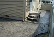 Stamped Concrete (also known as textured or imprinted concrete) / This versatile concrete is available in a variety of patterns and colors, creating the natural appearance of slate, flagstone, tile or brick at a more affordable price. An ideal outdoor paving option, it is often used for pool decks, driveways, entries, courtyards and patios. Stamped concrete also may be used for complex projects, commercial sites and in conjunction with other hardscape materials.