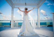 Real Bride Kerri / Custom design dress inspired by the Sousanna dress by The Cotton Bride.  Cotton/Silk blend fitted gown w/ beaded cummerbund detail & low V-back with covered button detail to hem.  Custom made-to-measure in the USA.  Price upon request.