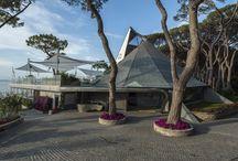 La Vela / progetto di Spagnulo&Partners per una Spa e Fitness Center di 330 mq al piano terra, un Ristorante e Bar con terrazza di circa 360 mq al primo piano, Beach Club e Bar esterno prospicente la spiaggia, una piazza circolare d'ingresso, ed il grande parco con pineta che circonda la struttura.