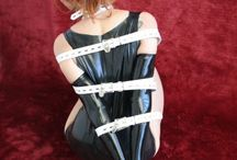 Strict leather strap bondage on sexy latex pinup girl