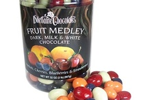 Chocolate Covered Fruit Anyone? / Get your hands on a truly delectable treat. Chocolate Covered Fruit Dragees from Dilettante make any occasion a special one. These delectable morsels are made in our special revolving kettles that coat each dried fruit piece with the best quality milk and dark chocolate. The final chocolate layer is white chocolate colored to a beautiful hue. Chocolate covered apricots, blueberries, cherries, strawberries, pineapples, mangoes, raisins, cranberries... Find your sweet indulgence!