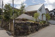 """西松ヶ丘の家 House in Nishimatsugaoka / [空気が循環する包容力のある家]自主性や創意のある子供を育てたい。広い庭で家庭菜園を楽しみたい。家族構成や趣味の変化に対応できる、許容力のある家に住みたい。そう考えて郊外に移転した施主の要望を、さまざまな工夫で叶えたのがこの家だ。その一つが1階のキッチンとダイニングの間にある作り付けのテーブル。ダイニングテーブルともキッチンカウンターとも違う、""""家事テーブル""""とでも呼ぶべきこの場所では家族がパン作りやアイロン掛けなどの家事を楽しみながらコミュニケーションをとる、家の中心になっている。 2階は将来、間取りを変更できるようにワンルームとした。天井は切妻屋根の勾配にあわせて斜めになっていて、家族をやさしく包む。1階のリビング・ダイニングの吹き抜けに面した内窓を開けると、家全体に一体感が生まれる。2階の階段上部には夫の書斎や子供の隠れ家に使えるロフトを設けた。とくに用途を定めない空間があることで暮らしに新しい風が吹く。"""