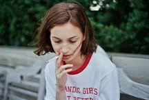 Lea / dark shoulder length hair, smoking, red lips, eyeliner, black tattoo, white sheets, note pads