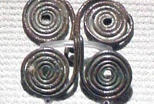 "Anglo Saxon Spiral Wrist Clasps / Used primarily in Anglian areas of England, often paired with Annular Brooches and Amber beads (specifically in the Castledyke Cemetery.) Hines Class A Sleeve Clasps are usually made of a single length of wire. Silver, copper-alloy, or the appearance of silver are all valid choices. ""Place"" names may be approximate, as the map function requires a specific location to work, and not all archaeological sites have places defined in the map function."