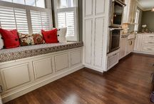 Upper Arlington Contemporary/Rustic Kitchen / This kitchen remodel in UA features custom cabinetry, a seating nook, pendant lighting, island with a stove top, mini bar area, rustic chandelier, and stainless steel appliances.
