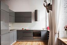 Kuchnie w dawnym budownictwie mają niepowtarzalny urok, który warto podkreślić ciekawymi meblami / W projekcie udało się połączyć funkcjonalne rozwiązania i nowoczesny design, który doskonale wkomponowuje się w wiekowe pomieszczenia. Minimalistyczna, uporządkowana bryła zabudowy efektownie kontrastuje z oryginalnymi elementami wnętrza (nieosłoniętą, surową cegłą wyeksponowaną na jednej ze ścian, drewnianą podłogą oraz, charakterystycznymi dla kamienic, wysokimi drzwiami i oknami).