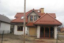 Projekt domu Klasyczny / Projekt domu Klasyczny przeznaczony jest dla cztero-pięcioosobowej rodziny. Jest to parterowy domek z użytkowym poddaszem, z dobudowanym garażem, przekryty czterospadowym dachem z lukarnami. Choć Klasyczny nie ma dużej powierzchni użytkowej, sprawia wrażenie tradycyjnej solidnej willi, z reprezentacyjnym frontem - zaakcentowanym szerokimi drzwiami wejściowymi z bocznymi naświetlami, oraz efektowną elewacją ogrodową - z dużymi przeszkleniami salonu i sypialni.
