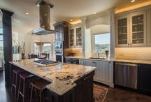 Castle Pines Saxeborough Drive / A combination of stain and paint colors with architectural features creates a stunning and impactful space. Item of note would be the structural column wrapped in matching cabinet materials and accented with molding. Designers: Jared Caruso and Mark Fergenbaum