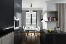 Apartament w ciemnych  barwach / Projekt wnętrza apartamentu został dostosowany do potrzeb jego właściciela. Apartament utrzymany jest w chłodnej kolorystyce jednak elementem ocieplającym wnętrze jest orzechowa podłoga. Architekt zaproponował grafitową cegłę, która pojawia się w salonie i kuchni, gdzie została dodatkowo podświetlona z poziomu blatu. Projekt mebli zakłada minimalistyczne formy, które utrzymane są w jednym stylu w całym apartamencie. Sprzęt grający stanowi idealne dopełnienie całości.