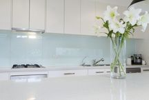 Glass / Custom-built glass Splashbacks. Bring rooms to life with durable and elegant coloured glass Splashbacks. Smooth and sleek, with modern lines and subtle or bold designs, coloured glass is a cost-effective way to bring absolute style and functionality into kitchens, bathrooms, laundries and home living areas. Installed without screws for a seamless finish, glass is durable, heat resistant, hygienic and easy to maintain.