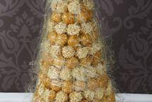 Крокембуш / Крокембу́ш (фр. croquembouche) — французский десерт, представляющий собой высокий конус из профитролей (заварных пирожных) с начинкой, скреплённых карамелью или специальным сладким соусом, и украшенный карамельными нитями, засахаренным миндалём, фруктами, засахаренными цветами. Используется как угощения в свадебных церемониях, при крещении, на Рождество.