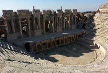 """Hierapolis -Pamukkale / Travertenlerin hemen üstünde Hierapolis Antik kenti yer alıyor.  Antik kentin, Arkeoloji literatüründe """"Holy City"""" yani ''Kutsal Kent'' olarak adlandırılması da, kentte bilinen birçok tapınak ve diğer dinsel yapının varlığından kaynaklanıyor.  Bilmemiz gereken sağlık ve güzellik amacıyla kurulan şehirden geriye kalan kalıntılar ve doğa harikası olarak nitelendirdiğimiz travertenlerle bütünlüğü ."""