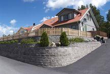 Inspirasjon EN MUR PÅ GRENSEN / En mur rammer inn, avgrenser og binder sammen. Den blir automatisk et naturlig blikkfang. Avhengig av form, farge og struktur framheves eller harmoniserer muren med resten av det omliggende miljøet. Skrånende tomter blir vakrere og mer praktiske takket være våre støttemurer som bygger opp nivåskiller og terrasseringer. Lave steinmurer rammer inn rabatter og holder vekster og jord på plass