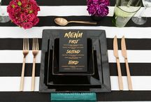 Modern Romantic / Bold black and white striped linen lay the base for this modern romantic style. Pops of fuchsia roses, peach David Austins with cascading greenery from gorgeously striped art deco shaped black vases. Copper foiled menus on black stock accented the matte copper cutlery beautifully and tied in the industrial feel of the black bentwoods and edison lighting.  See our stunning film at www.youtube.com/watch?v=RmLokuoM57E  Enchanted Empire