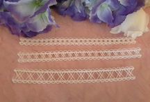 Lace / Lace is a fine open fabric of cotton or silk, made by looping, twisting, or knitting thread in patterns and used especially for trimming garments.
