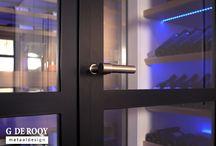Blaricum: dubbele glazen wijnkelderdeuren / In een villa in Blaricum hebben we een set prachtige stalen deuren met glas voor een wijnkelder mogen leveren. De dubbele glazen deuren sluiten de wijnkelder af, maar behoudt volledig zicht op de wijnflessen. De vijf-vlaks verdeling van de stalen deur geeft de wijnkelder een open en toch robuuste uitstraling. De deurgrepen zijn van Formani, de afwerking is een matte RAL9005 poedercoating