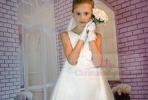 First Communion Dress of the Day Style 6834 / FIRST COMMUNION DRESS OF THE DAY! This beautiful first communion dress is satin with organza overlay beading throughout. Sleeveless tea length communion dress with satin bow accent. Zipper back. A Christian Expressions Collection best seller.