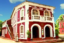 Panjim Peoples / An elegant and eye catching baroque mansion built in the early 1800s, WelcomHeritage Panjim Peoples was till recently home to the Peoples High School, Goa's premier English educational institution and alma mater to many of the state's prominent citizens. Opposite the Panjim Inn and prominently visible as you stroll down 31st January Road, it is now a Heritage Hotel and houses the inhouse Art Gallery Gitanjali.