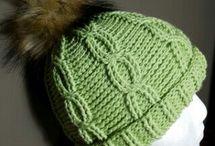 cappellino a trecce all'uncinetto con pon pon di pelliccia colorata.
