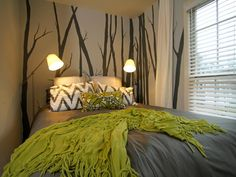 A painted tree mural accent wall lends a tranquil feel to this small bedroom. The gray backdrop in the mural provides a contrast to the lime green blankets and pillows that resemble foliage.