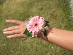 Gerbera wrist corsage for girl with orange gerbera and yellow solid aster filler and blue ribbon