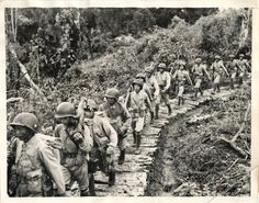 1943- American-trained Chinese troops, under the command of General Stilwell, march over jungle pathway near their encampment on the Northern Burma Front.