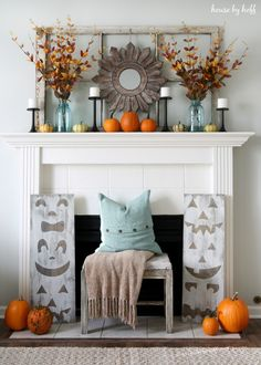 Wooden jack-o'-lantern signs stand tall below a mantel filled with candles, colorful pumpkins, and rustic leaves.