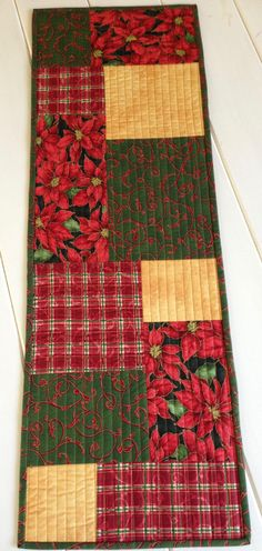 Reversible Quilted Christmas Poinsettia Table Runner in red, green and gold. Table Cloth for table or side board or bedroom dresser. Table topper, Quiltsy Handmade  This table runner can be used with either side up. There are four different fabric on the front in red, green and gold. The poinsettia fabric gives the table runner the Christmas theme. Finished size is approximately 12.5 X 35.5. All my products are made with quality quilting cotton fabric. All products are made in a smoke-free…
