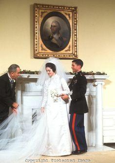 Former President Lyndon Johnson helps with his daughter, Lynda Bird Johnson's wedding dress on the day of her wedding, December 9, 1967.