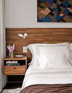 O pequeno gaveteiro, acoplado ao painel de cumaru, serve de criado-mudo no quarto projetado por Maicon Antoniolli.