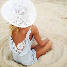 le chapeau de plage blanc bien combiné avec un combi-short bleu pour la plage