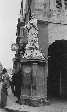 A view of the beautiful statue along St. Anne Street, Floriana looking in the direction of Valletta. People appear to be waiting for a bus. This area was very badly damaged by aerial bombing during World War Two and upon rebuilding this street was widened.