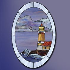 """An 18"""" x 24"""" oval stained glass panel featuring a beckoning lighthouse. Combinations of blues, purples, amber opals, and wispy glass bring the crashing waves on the rocky shoreline to life. The lighthouse catwalk, window details, and lightning rod are added using copper wire. This project was constructed using the copper foil technique."""